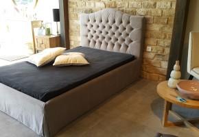 מיטה מרופדת עם קפיטונאזי בראש מיטה ו חצאית מסביב ה מיטה